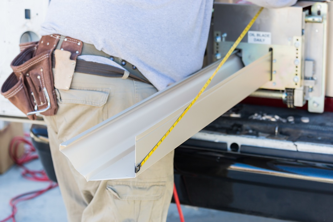 Worker Measuring An Aluminum Rain Gutter Feeding Through Seamless Shaping Machine.
